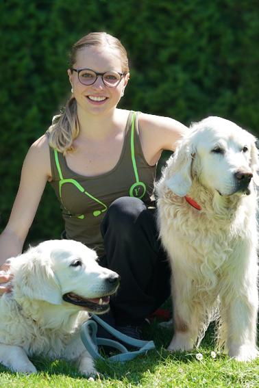 Amélie Jampen sitzt mit zwei Golden Retriever im Garten der Klinik